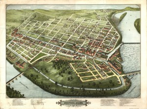 View from above of green land encircled by the Connecticut River, showing bridges, dam, and grid of streets and canals with brick factories and smaller houses.