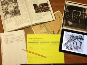 A desktop contains a textbook, ipad, historic map of immigration routes, and the Library of Congress analysis tool.