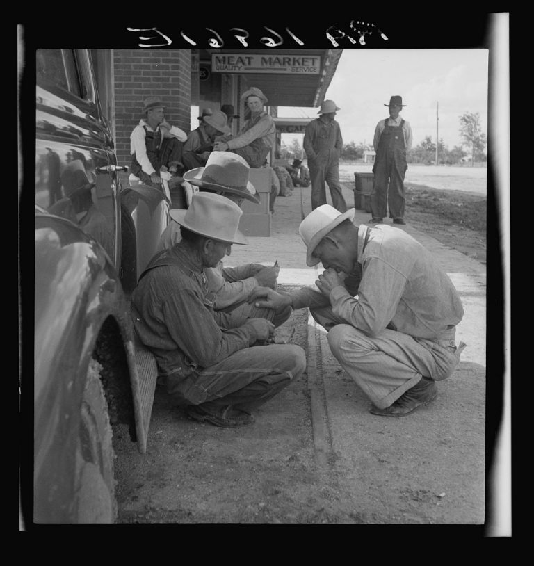 men in overalls and hats squat in the shade of a car as others stand in the background.