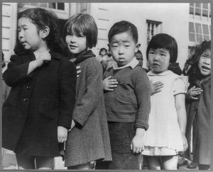 Japanese children with their hands covering their hearts