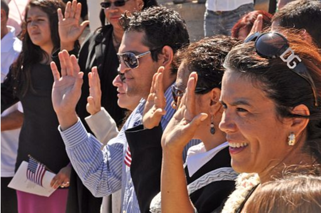 Image of new citizens holding up their right hand as part of an oath of allegiance in a citizenship ceremony.