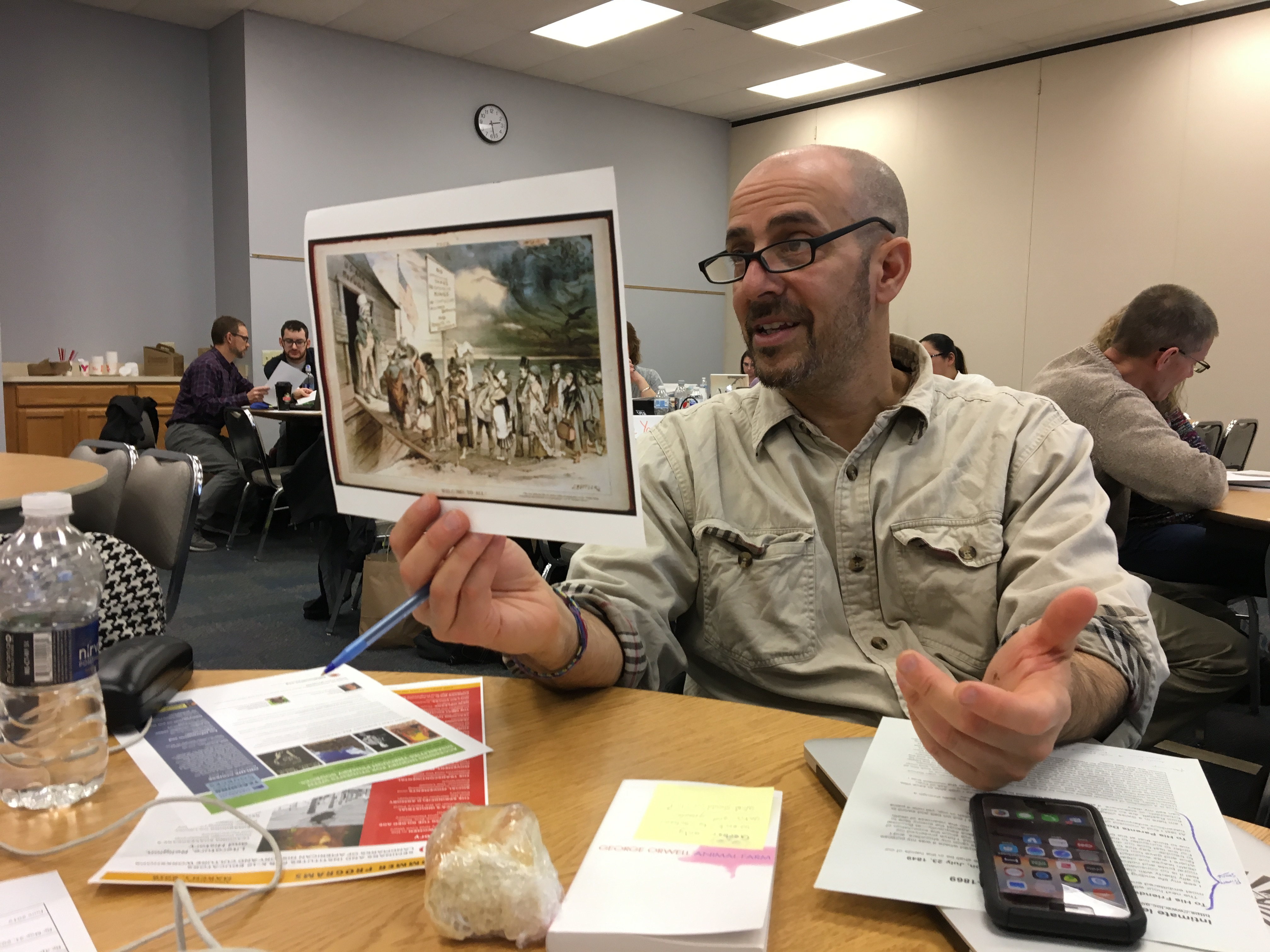 Man holds up a color print of an 19th c. cartoon as he gestures with his free hand.