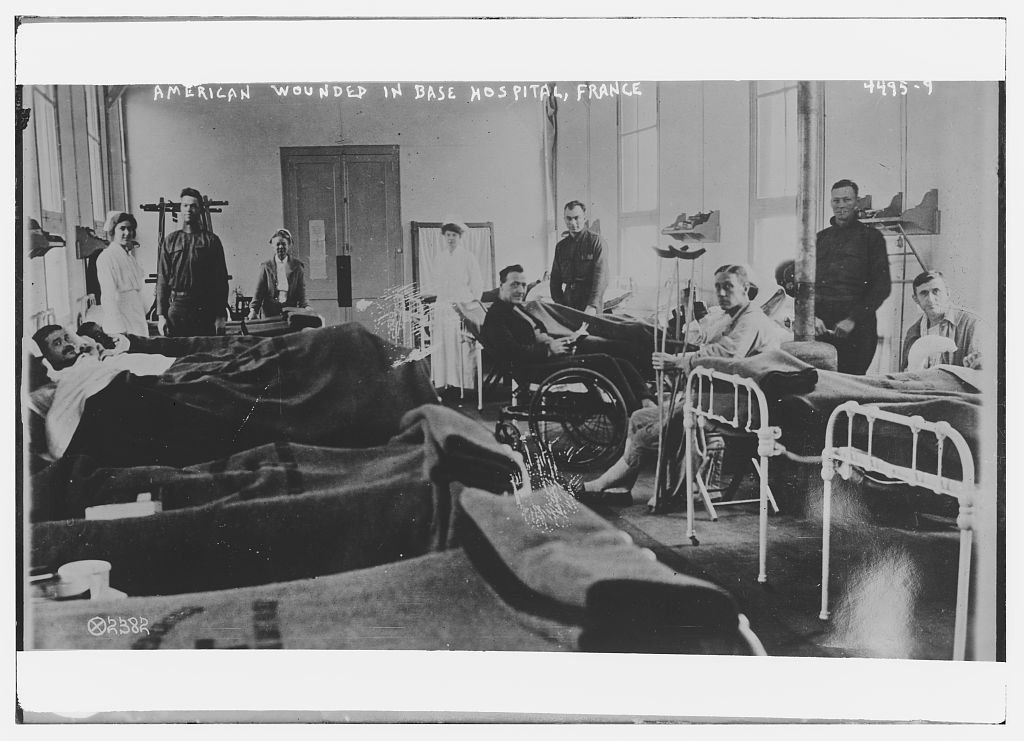 A room with at least 5 iron beds with patients lying or sitting up, other convalescing soldiers have crutches, a wheelchair, and a wheeled bed, and 3 white-capped uniformed female nurses and 3 men in soldiers uniforms stand in the background , France,1917 or 1918