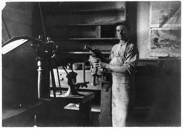 Young man wearing apron stands by machine in factory workshop.