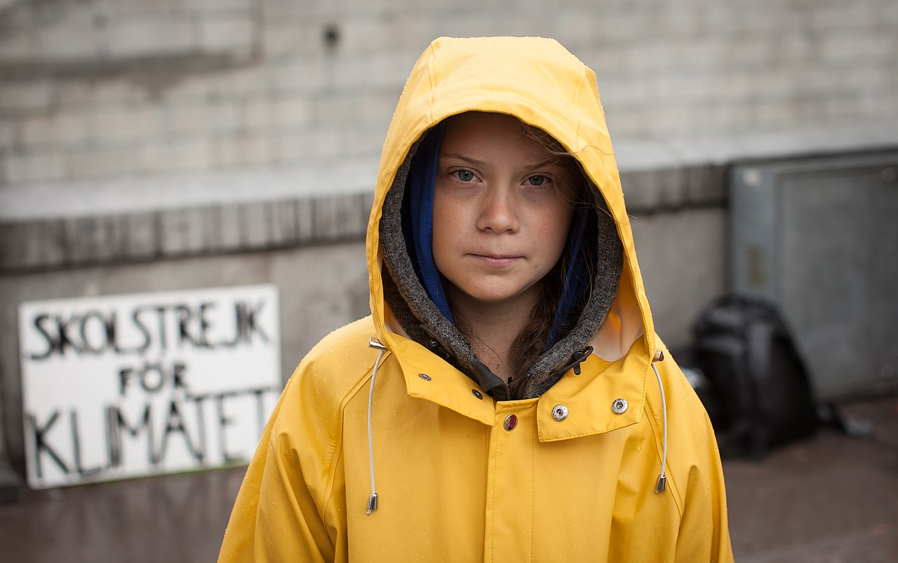 "Teenage activist Greta Thunberg stands outside wearing a hooded yellow raincoat, ""Skolstrekt for Klimatet"" sign behind her [school strike for climate]"