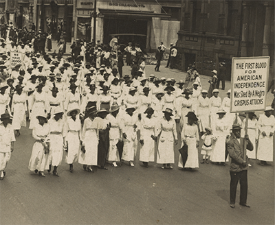 thousands of black women wearing white long dresses and some men in suits march in a 1917 New York City street. Three protest signs are visible.
