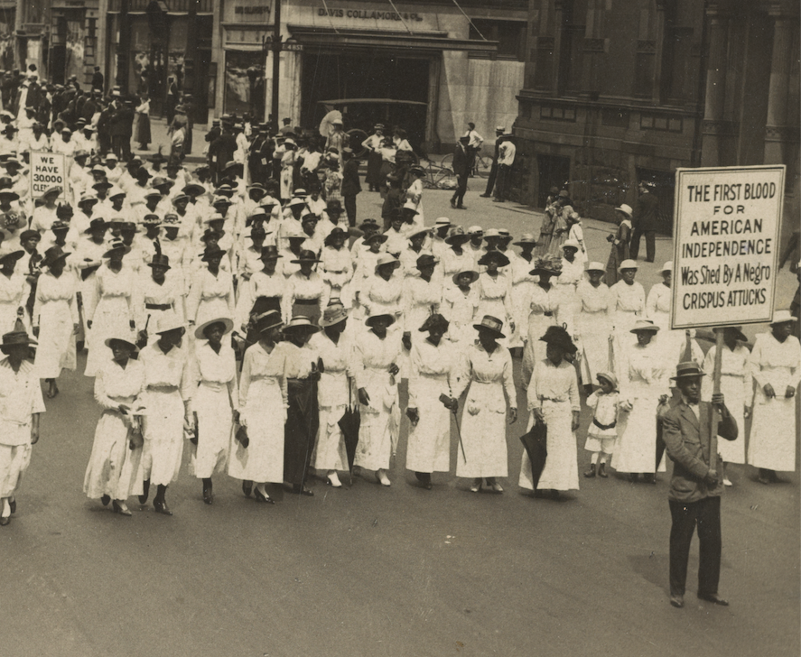 "Rows of African American women wearing long white dresses, arms linked, fill a city street, led by a man holding a sign reading, ""The First Blood for American Independence was Shed by a Negro: Crispus Atticus"""