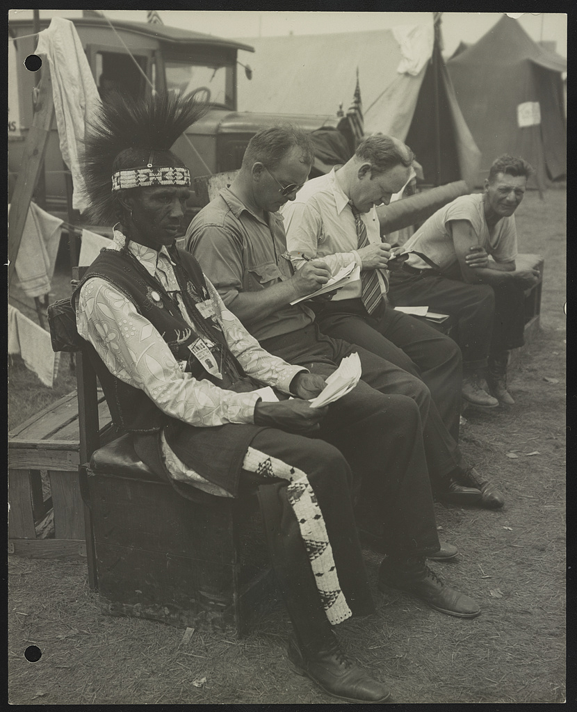 Photograph shows four men, probably veterans, sitting on a bench with tents in the background, probably at the Bonus Expeditionary Forces assemblage in Washington, D.C. One of the men is wearing a traditional Indian headdress, and pants and a vest with Indian motifs.