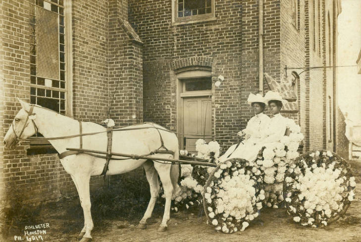 Two young Black women in white hats and long dresses sit in an open carriage with flower-decorated wheels drawn by a white horse in front of a brick building