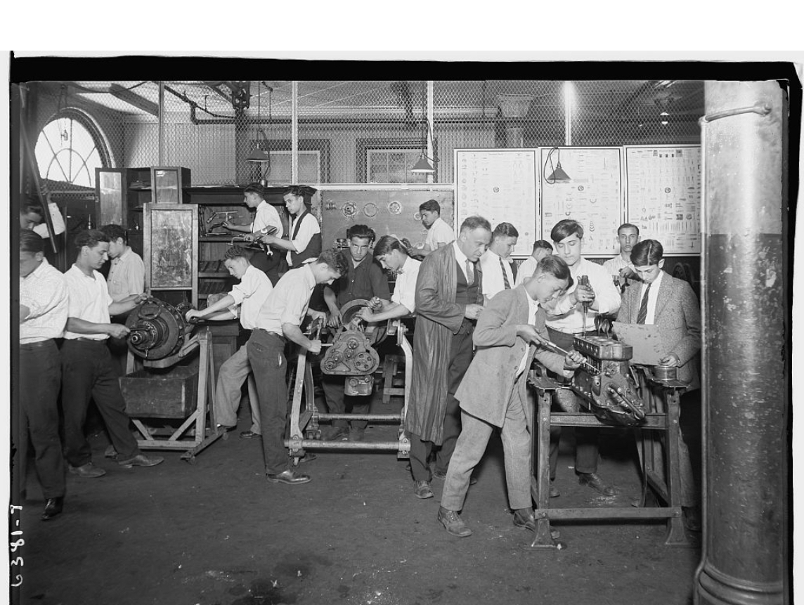 Youths work in a machine shop supervised by a man in a long coat.