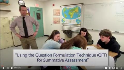 Screen cap of teacher looking over students working in team.