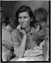 A woman with tired children leaning on each shoulder looks worried as puts her hand to her face in a black and white photo.