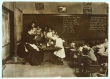 A classroom with students working at desks, teacher in long dress seated at a table next to chalk boards, surrounded by a group of 6 girls of varied heights, using her hands as she explains something.
