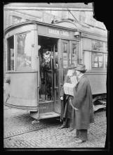 Streetcar with surgical-mask-wearing conductor, waves goodbye to two men on street wearing hats & overcoats, one wearing improvised mask.
