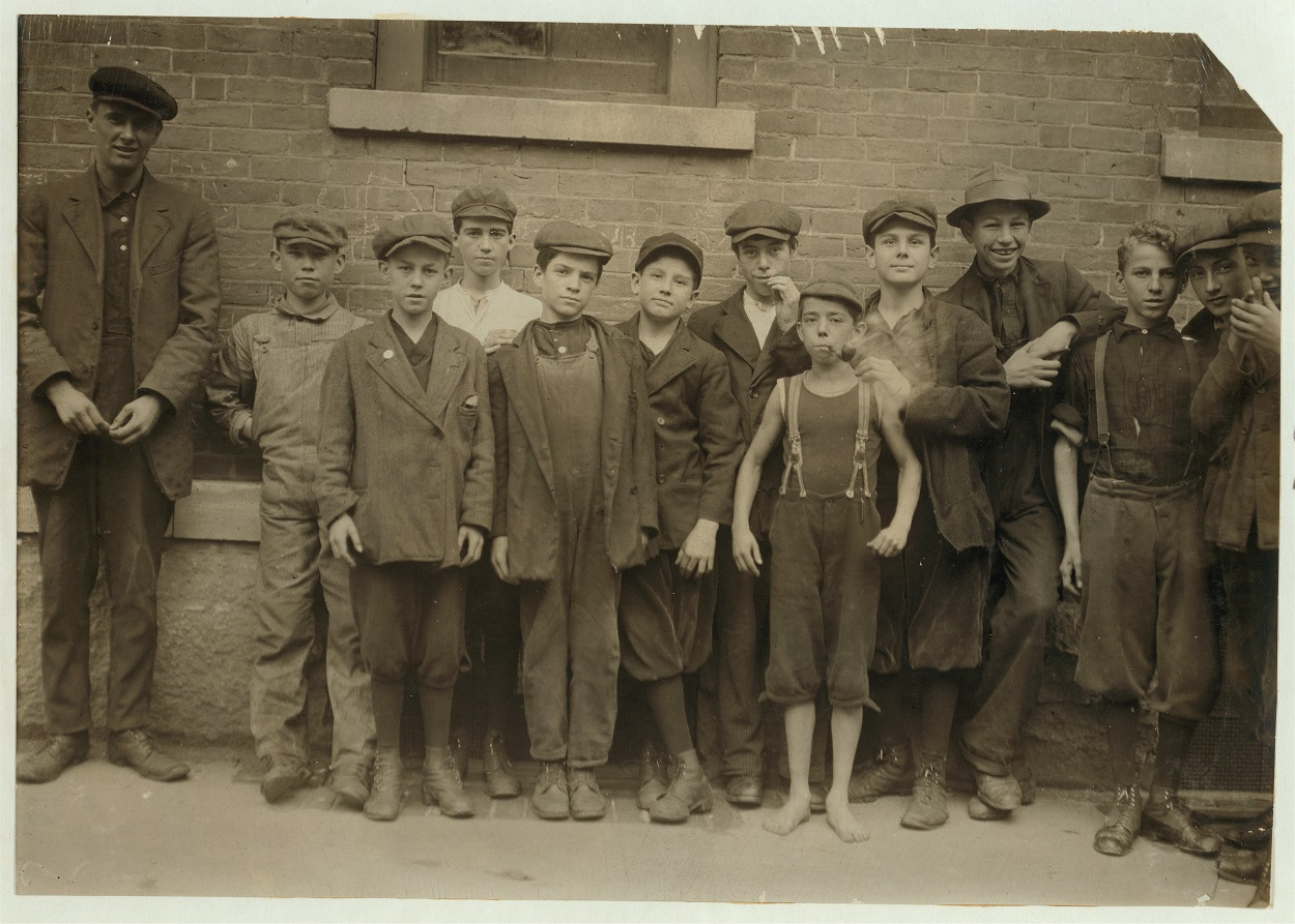 Child Laborers from 1911 (10 boys) pose in a line next to a man, no child taller than his shoulder