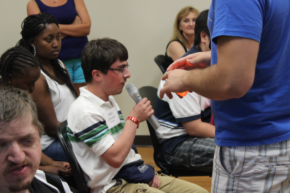 student speaks into a microphone at a community meeting