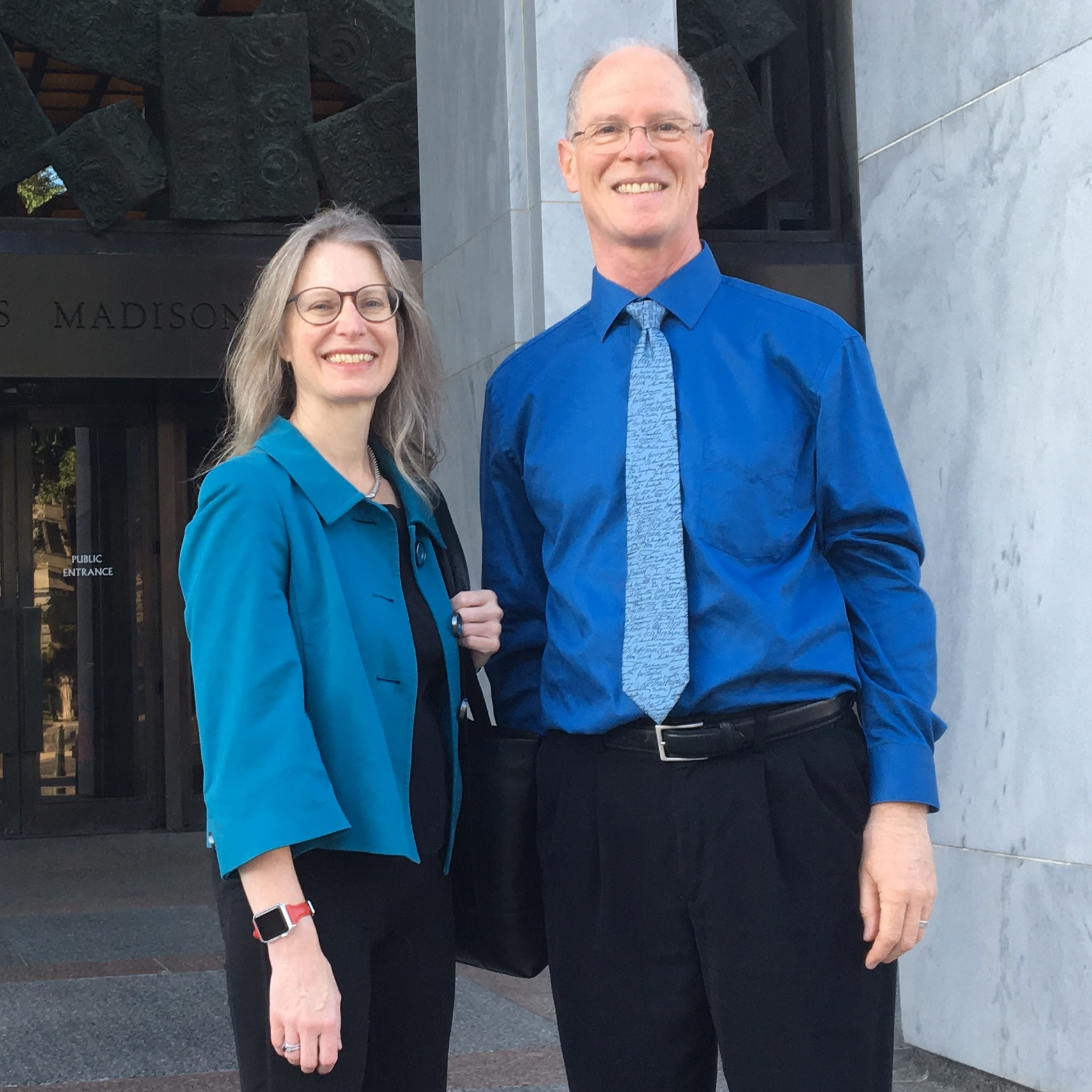 Alison Noyes and Rich Cairn smile as they stand in front of Madison Building of the Library of Congress.