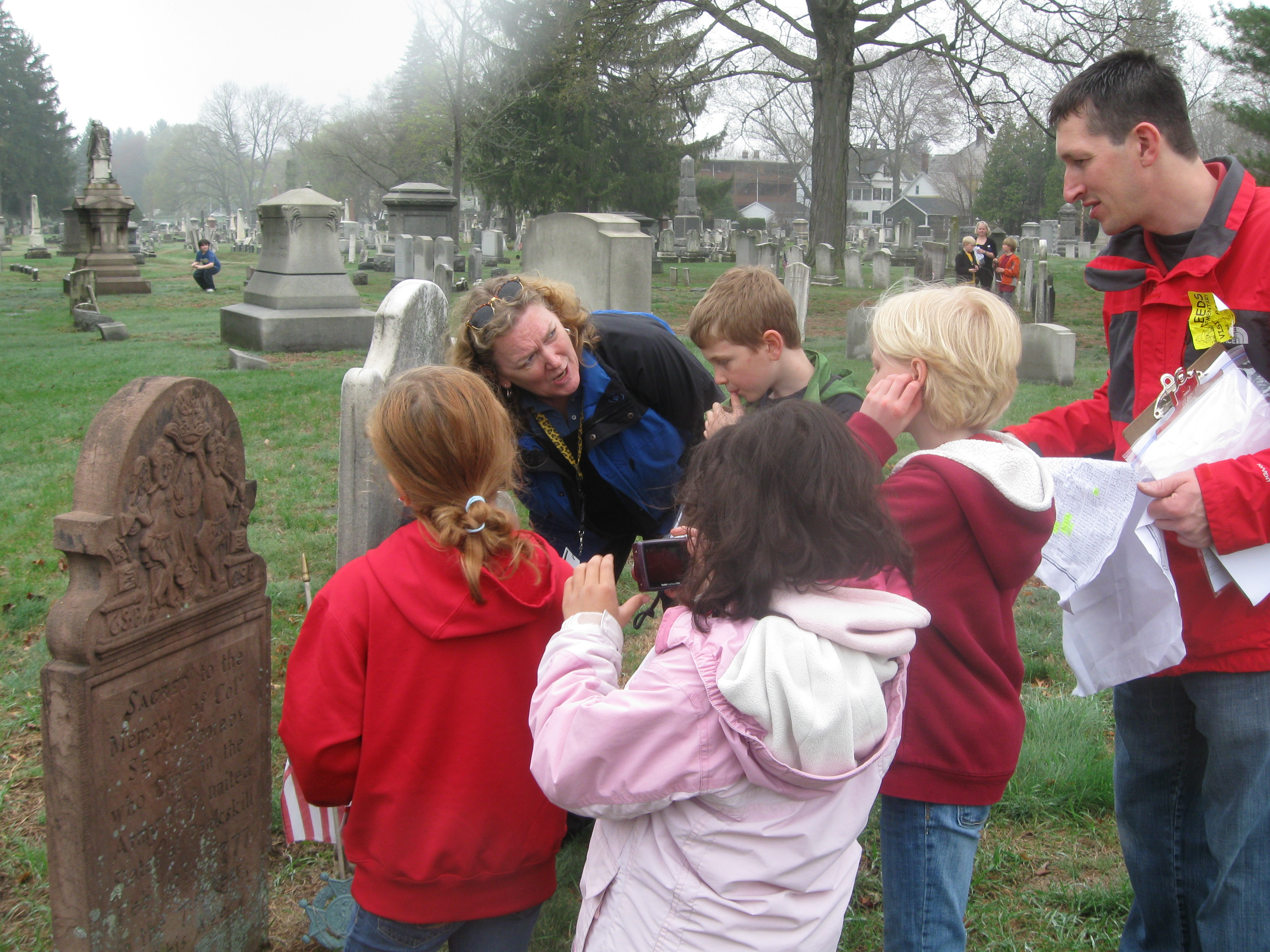 Header Photo - Denise Wood, Leeds Elementary School, Northampton, leads students in a study trip to the Bridge Street Cemetery in search of stories of Revolutionary War soldiers.