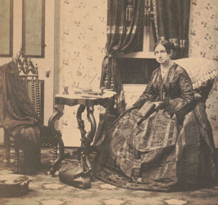 Dorothea Dix in a long dress holds a book and sits in a room with a medical bag on the floor