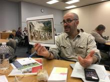 Teacher holds up a political cartoon primary source.